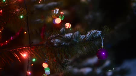 nativo : Glowing garlands of bokeh and festive colored tinsel decorate dark spruce branches with a ball on the street shaking in the wind on new years eve against the background of snowdrifts. Stock Footage