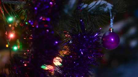 pozlátko : The festive decoration of the Christmas tree is a ball shaking on a branch in the street in the wind on a background of white snow with tinsel and bokeh light from the garlands on the trees on Christmas night. Dostupné videozáznamy