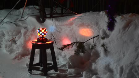 disko : Disco ball spinning on a wooden chair under the Christmas tree throwing multicolored glare on the snow holiday night.