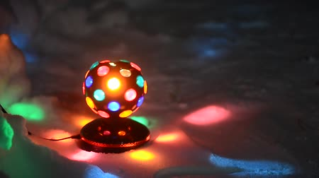 piscar : The old Disco ball spinning while standing on the white snow under the Christmas tree casting colorful reflections of the festive night.