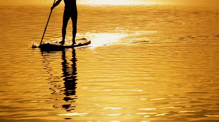 remo : A young man floats slowly on the paddle board