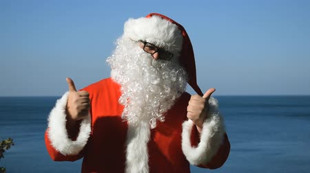 странный : A man in a Santa Claus costume is dancing on the seashore. Travel and vacation Стоковые видеозаписи