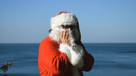 восхищенный : A man in a santa slaus costume on the seashore. Christmas in the tropics