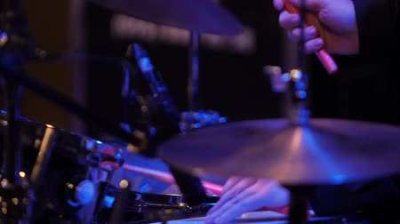 The drummers hands beat a beat.Closeup view of a drum set in a dark studio. Black drum barrels with chrome trim. The concept of live performances