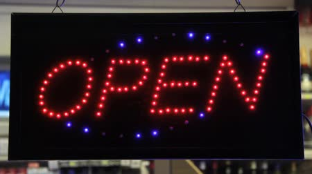 entrance : Open sign of a store with customers. Find similar clips in our portfolio. Stock Footage