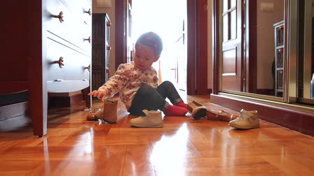 Пол : Curious baby girl trying on different shoes sitting put over a wooden floor at home