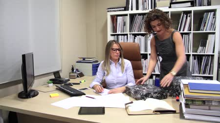 стулья : Unhappy blonde secretary receiving lot of work from woman chief in the office