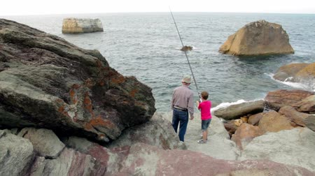 Back view of unrecognizable child fishing with a rod on the sea next to senior man standing over the rocks Stock Footage