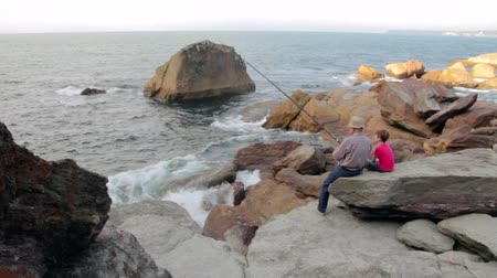 Back view of child and senior man fishing with a rod on the sea sitting in a rocky coast Stock Footage