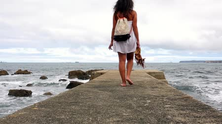 Back view of unrecognizable woman with bag in her back walking along of pier and looking to the sea in a cloudy day Stock Footage