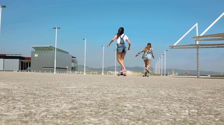 Back view of two unrecognizable young women having fun skating together on beach promenade in a sunny summer day