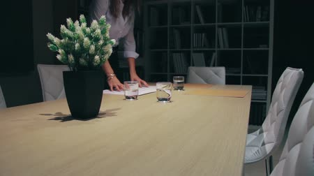 Unrecognizable woman putting folders with business documents over table for a meeting in office