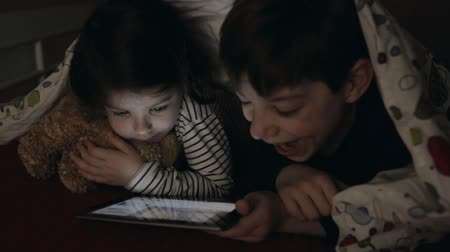 утешитель : Brother and sister lying on the bed looking at the tablet in the dark Стоковые видеозаписи