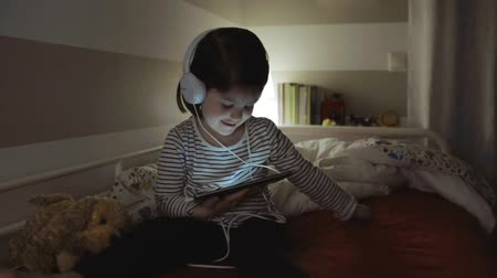 gesticulando : Funny girl with headphones dancing while looking at the tablet sitting on the bed at night Vídeos