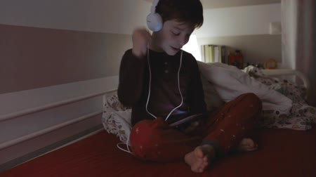 Funny kid with headphones dancing while looking at the tablet sitting on the bed at night Stock Footage