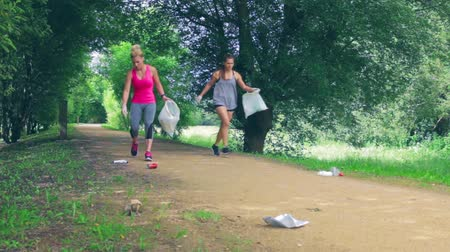 Waste pile and two girls running with bags doing plogging outdoors Stock Footage