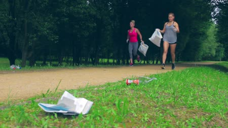 Girl crouching with bag picking up trash doing plogging Stock Footage