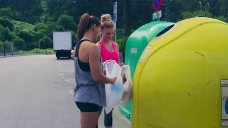 pull out : Two girls throwing garbage to recycling dumpster after plogging