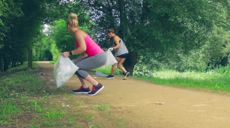 Two girls on back with garbage bags doing plogging Stock Footage