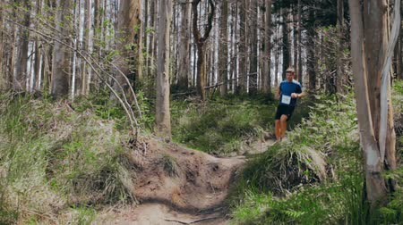 Young man jumping participating in a trail race through the forest