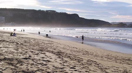 People on the beach at sunset: walking, sitting and surfing Stock Footage