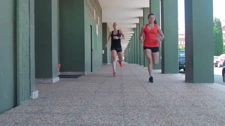 Two female athletes running through the arcades of a building