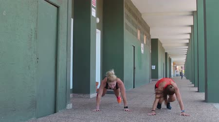 oneself : Two female athletes doing burpee exercise and lying on the floor tired