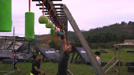 Male participant in an obstacle course doing suspension ring exercises Stock Footage