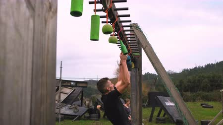 Male participant in an obstacle course doing suspension exercises