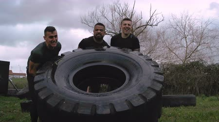 işbirliği yapmak : Group of participants in an obstacle course turning a truck wheel