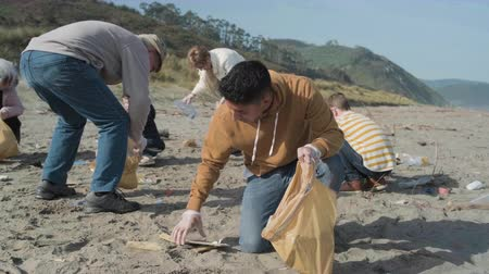 işbirliği yapmak : Young man with thumb up picking trash with group of volunteers on the beach