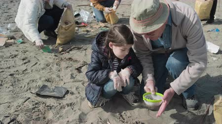 işbirliği yapmak : Grandfather and granddaughter volunteers picking up microplastics on the beach Stok Video