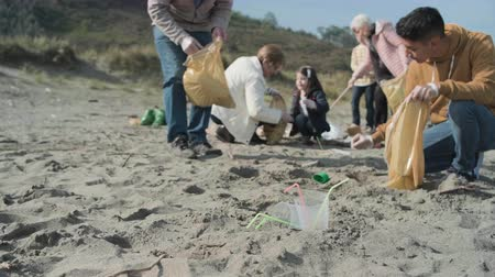 Plastic cups and straws on the beach with group of volunteers cleaning in the background. Selective focus in foreground Stock Footage