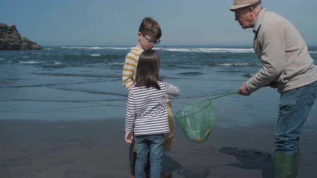 Grandfather and grandchildren taking garbage out of the sea with a fishing net