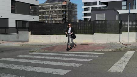 szandál : Slow motion of fashion businesswoman crossing the street on electric scooter on the sidewalk Stock mozgókép