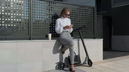 szandál : Businesswoman using mobile sitting on a wall with her scooter next