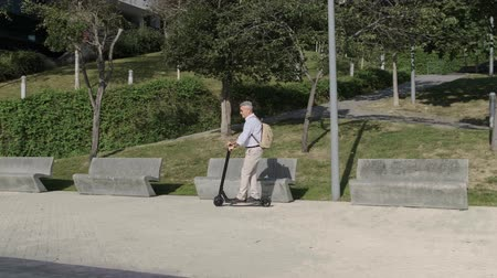 Senior man riding on electric scooter in a park
