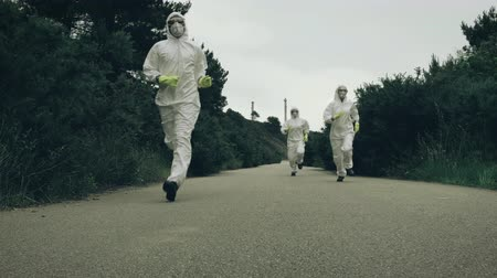 bacteriological : People with bacteriological protection suits running away on a lonely road