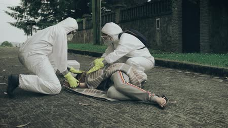 bacteriological : Man and woman in bacteriological protective suits running to help a woman passed out on the floor
