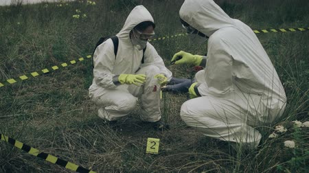 evidência : Two people with bacteriological protection equipment picking up evidence into a plastic bag next to corpse outdoors