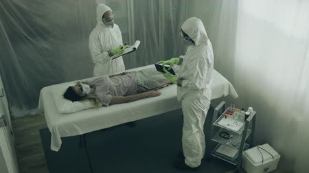 bacteriological : Two scientist attending to a woman with a virus lying on a stretcher in a field hospital
