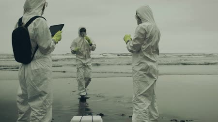bacteriological : People with bacteriological protection suits analyzing seawater on the beach Stock Footage