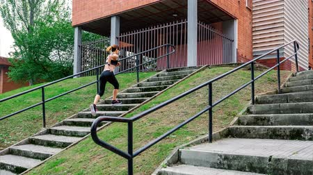 Young female athlete going up and down stairs outdoors