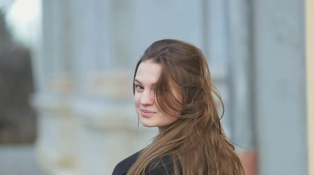 plášť : Fashionable glamorous young girl with long hair wearing black coat walks and pose at camera. Fashion vogue style outdoor portrait. Steadicam, slow mo shot