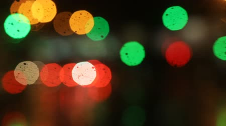 wiper : Multicolored bokeh from street and traffic lights at night. Car wiper works, raininng