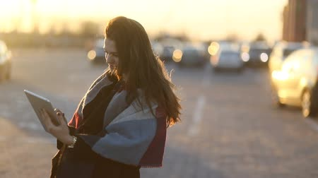 Young smiling woman with the scarf using tablet computer outdoors in the parking place. Marvelous sunset. Slow mo, steadicam