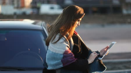 Beautiful girl with the scarf looking in tablet outdoors in the street near car. Looks around. Slow mo, steadicam Stock mozgókép