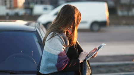 Suspicious girl with the scarf massaging tablet outdoors in the street leaning on car. Slow mo, steadicam Stock mozgókép