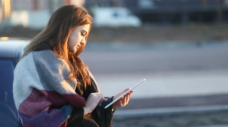 Young smiling girl with the scarf using tablet computer outdoors in the street sitting near car sending massages. Slow mo, steadicam Stock mozgókép