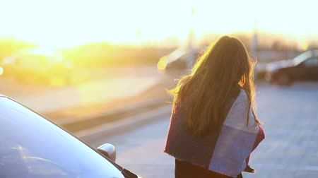 Young girl looking on the sunset leaning on car. Than turns to the camera. Shining sun Stock mozgókép